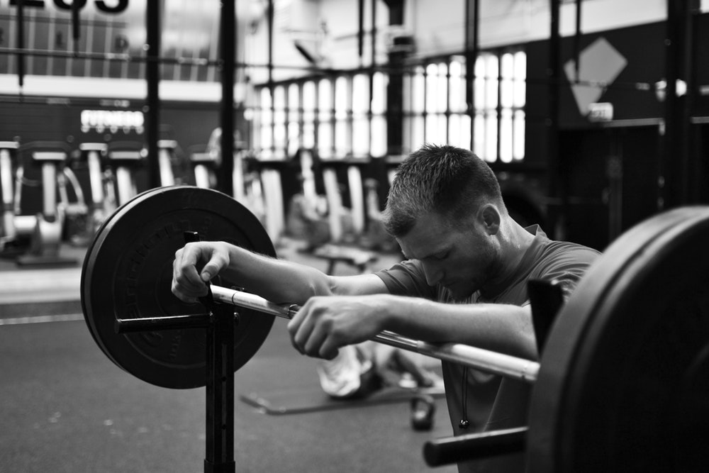 gray scale photo of man sitting on bench press